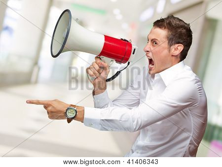 Portrait Of Young Man Shouting On Megaphone, Indoor