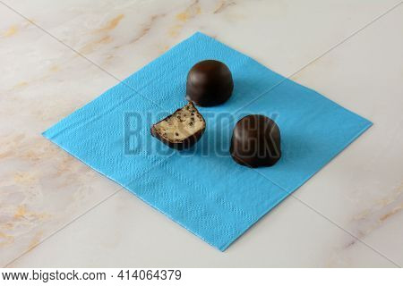 Stracciatella Balls Dipped In Chocolate With One Partially Eaten On Blue Napkin