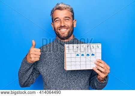 Young handsome blond man with beard holding weather calendar showing rainy week smiling happy and positive, thumb up doing excellent and approval sign