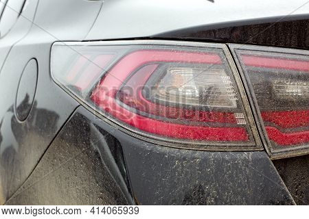 Taillight With A Red Brake Light And A Turn Signal Covered With A Layer Of Dust And Dry Dirt Close-u