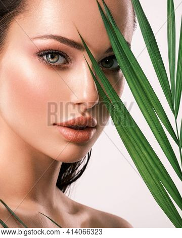 Young beautiful woman with green leaves near face. Skin care beauty treatments concept.  Closeup girl's face with green leave. White model with clean, health skin of face - posing at studio