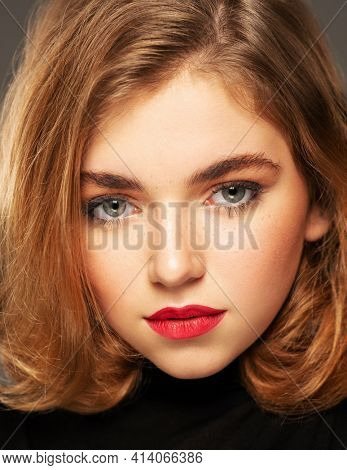 Closeup portrait of an young adult girl with medium length hair.  Photo of a fashion model posing at studio. Pretty young woman with red lips looking at camera. Beauty portrait.