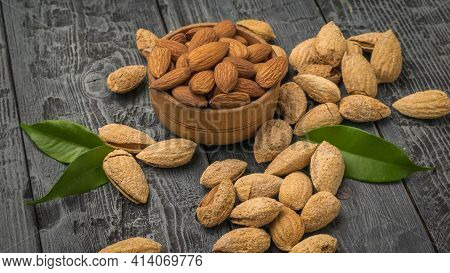 Scattered On A Wooden Table Are Unpeeled Almonds And A Wooden Bowl With Peeled Almonds. Vegetarian F