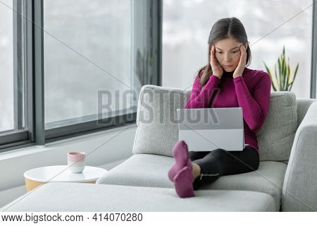 Computer problem laptop not working at home frustrated Asian woman with headache trying to understand online work or issue.