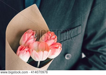 Elegant Man Holding A Bouquet Of Pink Tulips Wrapped In Craft Paper. Surprise For Your Beloved Woman