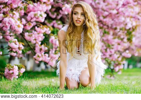Beautiful Young Woman In White Glamour Dress On Green Grass In Spring Pink Flowers Bloom. Daisy Flow