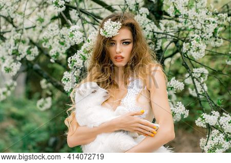 Fashion Portrait Of Young Beautiful Woman Holding A Small Lamb In Spring Blooming Garden