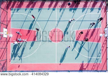 Young Adult People Play Basketball At Court. Men Play Streetball At Outdoor Court Top Down Aerial Vi