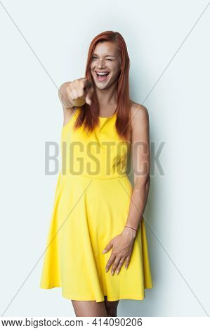 Red Haired Woman Is Smiling At Camera Blinking And Pointing Wearing A Dress On A White Studio Wall