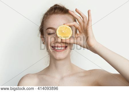 Ginger Woman With Freckles Is Smiling Covering Her Eye With A Sliced Lemon On A White Studio Wall