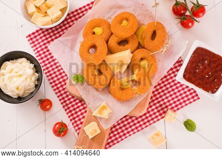 Fried Cheese Ring With Dipping Sauce On Cutting Board.