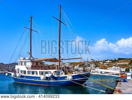 Sailboat Moored At Jetty Of Greek Island. Whitewashed Houses Waterfront. Summer Sunshine, Vacations,