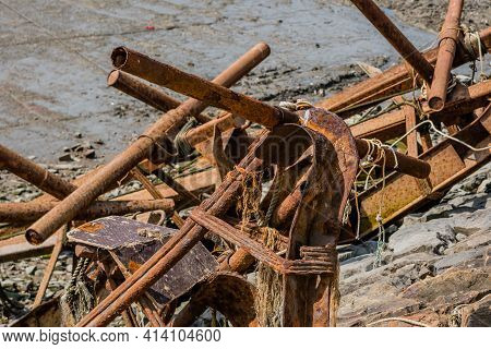 Large Rusty Ship Anchors Laying On Side Of Seawall With Water In Background.
