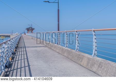 Long Concrete Pier With Wooden Gazebo N Alcove And Unrecognizable Tourists In Distance.