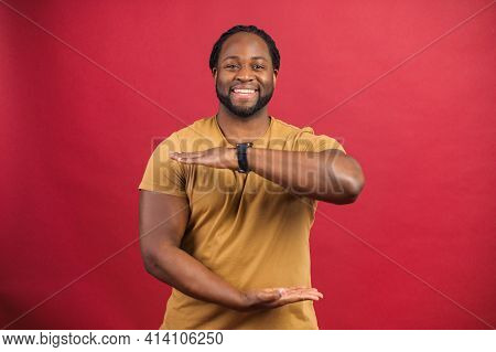 Portrait Of Smiling Young Handsome African American Guy In Yellow T-shirt Standing Isolated Over Red