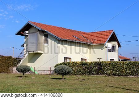 Curiously Looking Newly Built Suburban Family House With New Light Yellow Facade And Bright Red Roof