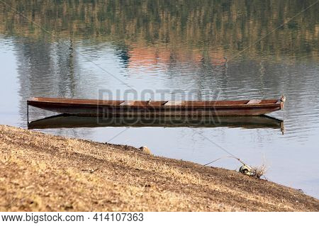 Elongated Old Dilapidated Light Brown Wooden River Boat Made From Wooden Boards Left Tied With Ruste