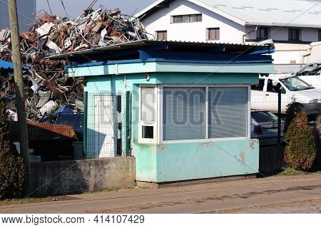 Old Dilapidated Light Green Guard House With Closed Window Blinds And Cracked Facade On Side Of Pave