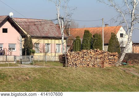 Row Of Partially Renovated Colorful Small Suburban Family Houses With Stacked Firewood Prepared For