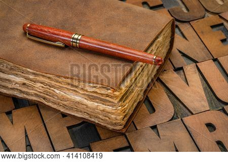 antique leatherbound journal with decked edge handmade paper pages and a stylish pen on a letterpress wood type alpahbet, journaling concept
