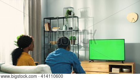 Rear Of Happy African American Couple Man And Woman Sitting On Couch In Living Room Watching At Tv M