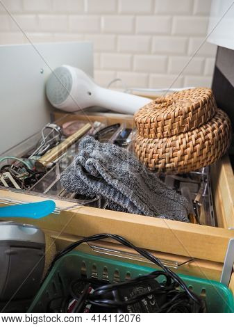 Messy Open Bathroom Drawer With Washcloth, Cosmetics And Hairdryer