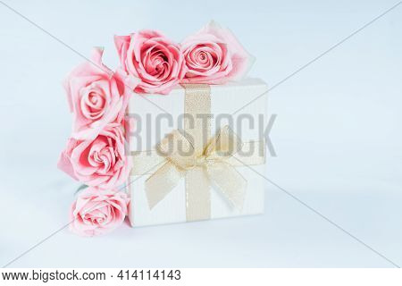 Beautiful Bouquet Of Roses With Gift Against Blue Background. Free Space For Text