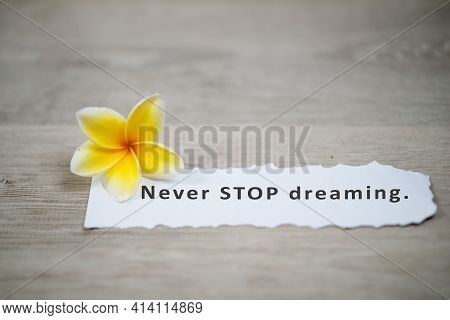Motivational Quote - Never Stop Dreaming. Positive  Note Message On A White Notepaper With Yellow Ba