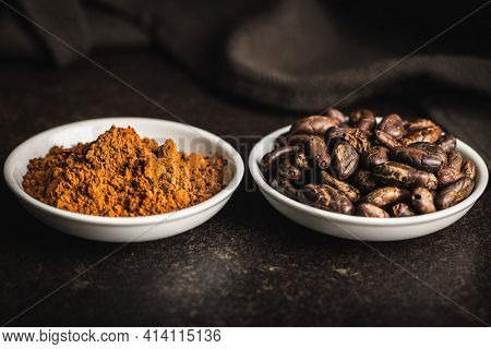 Cocoa powder and cocoa beans in bowl on black table.