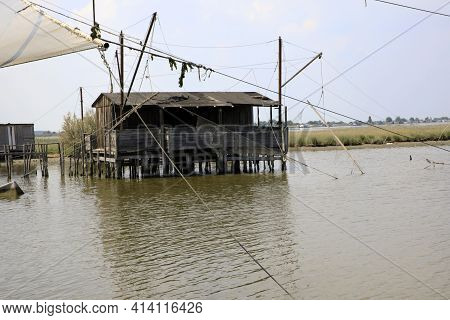 Po River (fe),  Italy - April 30, 2017: An Old Fisherman\\\'s House With A Net On Po River, Delta Re