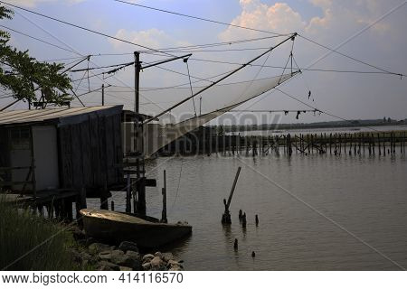 Po River (fe),  Italy - April 30, 2017: An Old Fisherman\'s House With Nets On Po River, Delta Regio