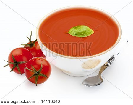 Bowl With Tomato Soup (gazpacho, Tomatoes, Basil Leaf And Spoon. Isolated On White Background. Medit
