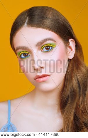 Make-up and cosmetics. Close-up portrait of a beautiful girl with bright colorful make-up on a yellow background.