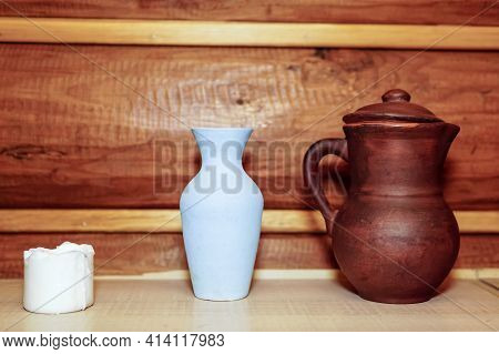 A White Burnt-out Candle. An Earthenware Jug. Ceramic Vase