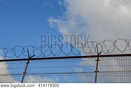 High Fence With Barbed Wire Wound On An Endless Barbed Prickly Spiral. The High-speed Train Track Is