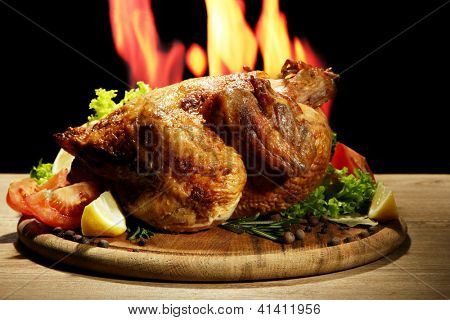 Whole roasted chicken with vegetables on plate, on flame background poster