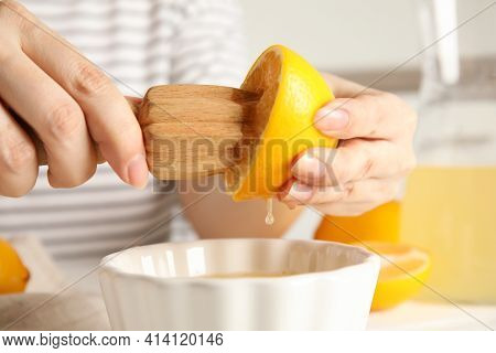 Woman Squeezing Lemon Juice With Wooden Reamer, Closeup