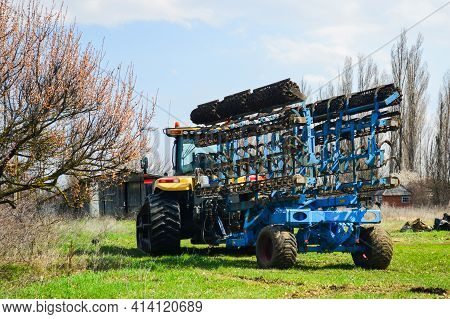 The Tractor With Modern Farm Equipment, Cultivator Or Plow.
