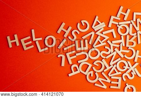 Top View Closeup Detail Macro Of Many Wooden Cut Small Alphabet Letters On Orange Background Spellin