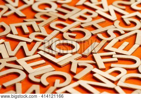 Perspective View Closeup Detail Macro Of Many Wooden Cut Small Alphabet Letters On Orange Background