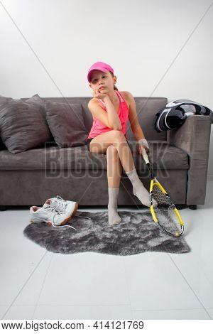 Bored Girl In Times Of Quarantine Sitting On The Couch And Holding A Squash Racket. Boredom In Home