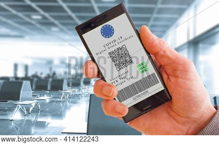 Mobile phone in hand  with digital green certificate of vaccination covid-19. Cell Phone screen with information on vaccination and antibodies to covid against background interior of airport. Covid