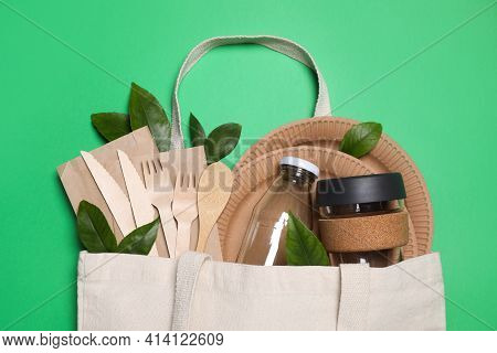 Flat Lay Composition With Eco Friendly Dishware In Bag On Green Background, Top View