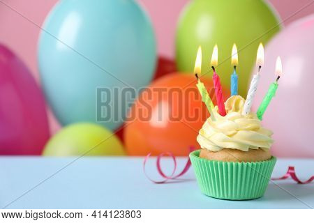 Birthday Cupcake With Burning Candles And Streamer On Light Blue Table Against Color Balloons. Space