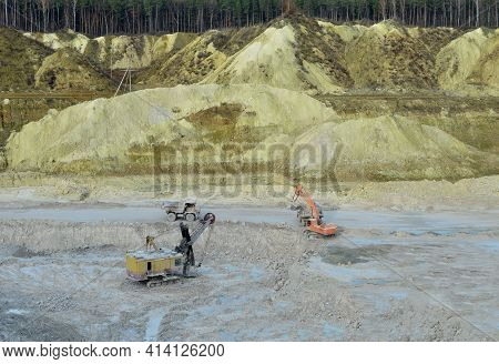 Excavator In Quarry Loads Rock Into A Mining Truck. Excavators And Trucks Work In A Chalk Open Pit.