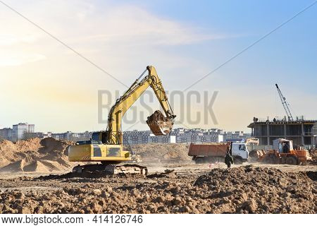 Excavator Digging Sand And Loading Into Dump Truck On Construction Site. Backhoe Digs The Ground, Fo