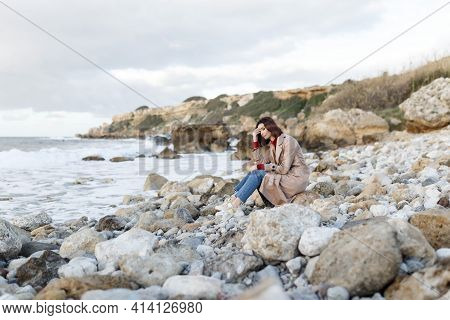 A Beautiful Young Woman Sits On A Rocky Shore And Thinks About Something. Evening Portrait Of A Beau