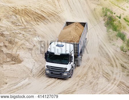 Truck With Tipper Semi Trailer Transported Sand From The Quarry. Dump Truck Working In Open Pit Mine