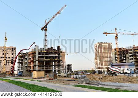 View Of Large Construction Site. Tower Cranes In Action. Formworks And Pouring Concrete Through A On