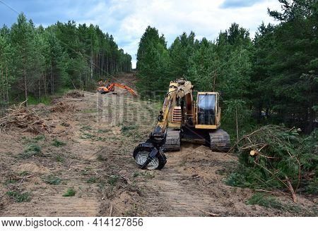 Excavator Grapple During Clearing Forest For New Development. Tracked Backhoe With Forest Clamp For